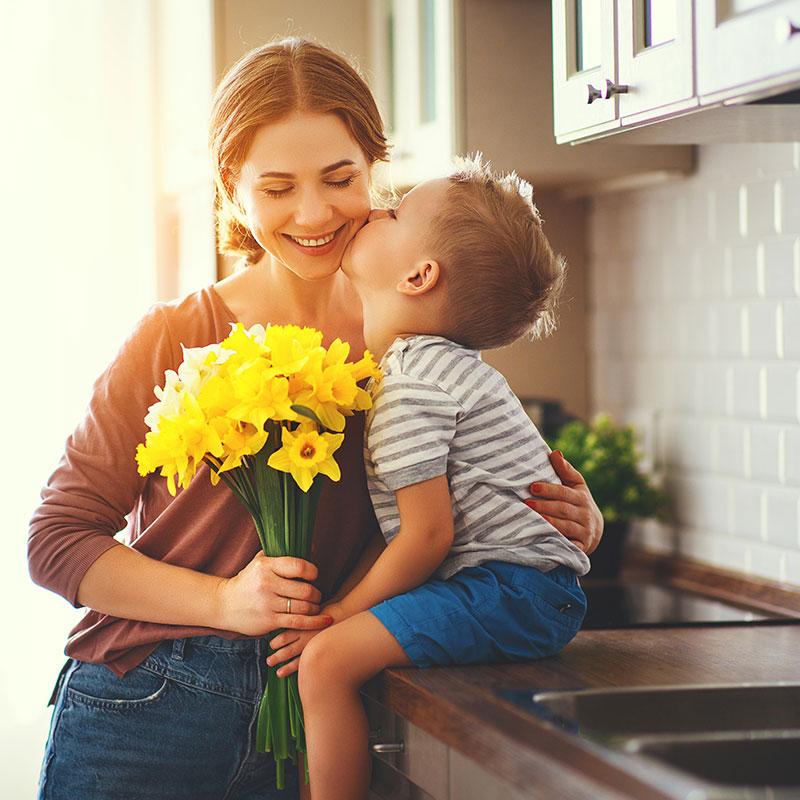 son-kissing-mom-in-kitchen-sq