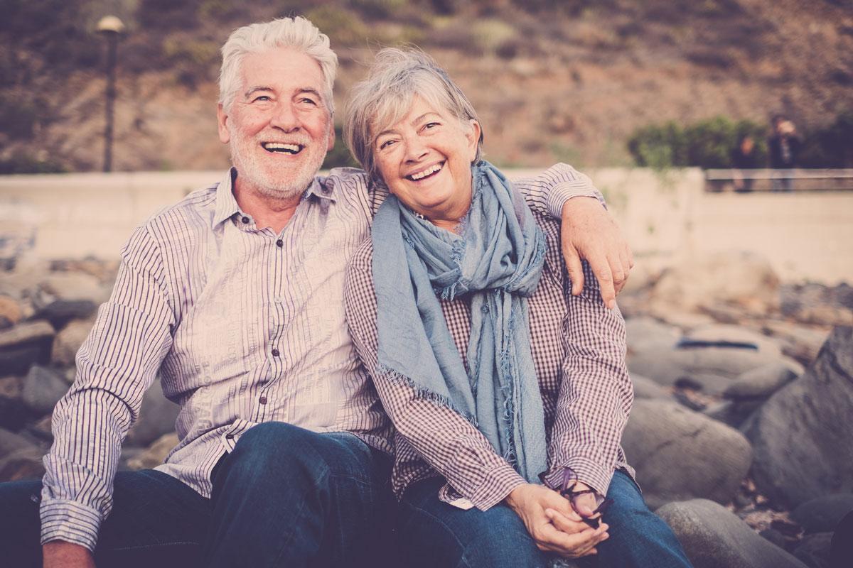 happy-elder-couple-sitting-at-park-bench
