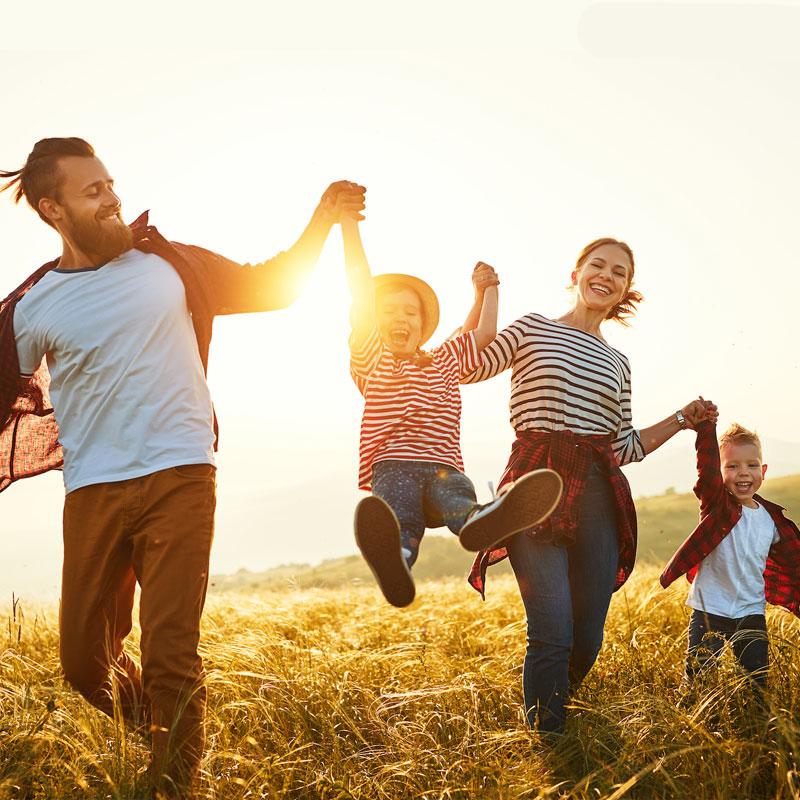 happy family walking through fields