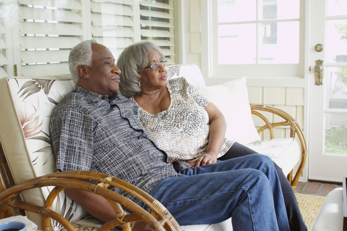 old-black-couple-sitting-on-their-porch-home